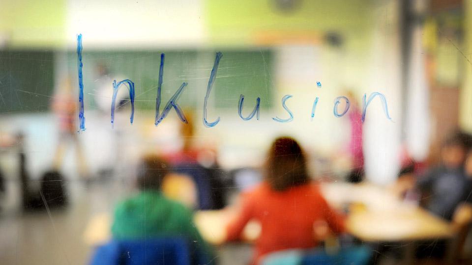 Das Wort Inklusion auf die Fensterscheibe einer Schule geschrieben