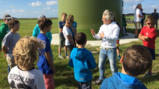 Kinder und Veranstalter stehen vor einer Windkraftanlage.