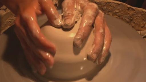 Hände halten Ton auf Scheibe.